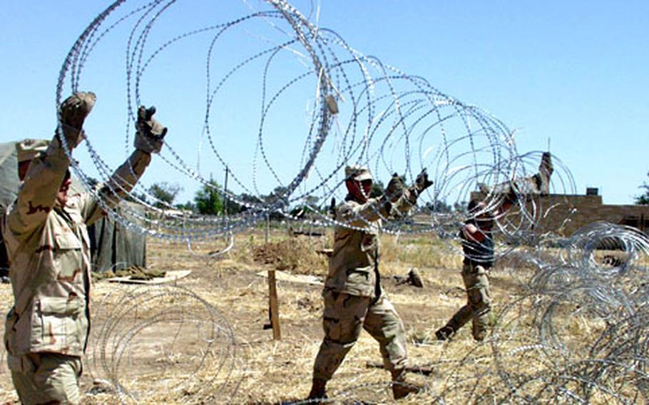 Master Sgt. Daniel Wear, Staff Sgt. Chip Davidson, and Staff Sgt. Brian Curtis, left to right, hoist a strand of concertina wire to help secure a living area.
