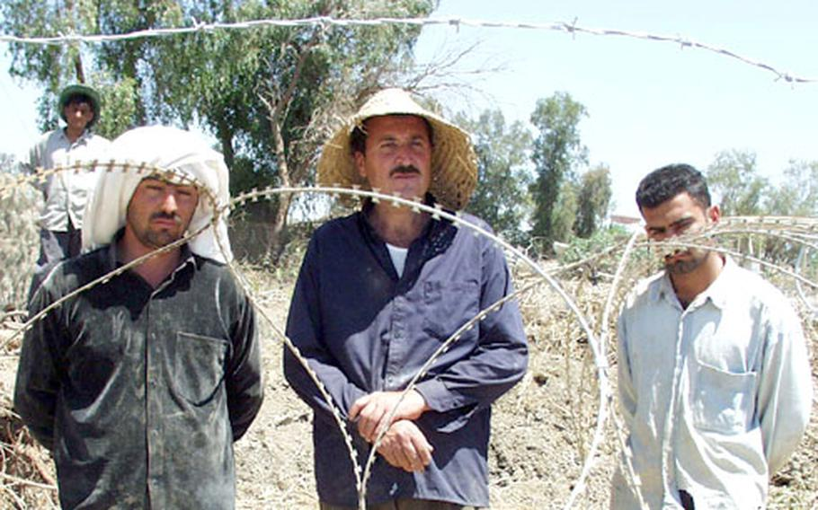 Ibrahim Adham, left, Azad Karim and a friend said they are dismantling buildings just beyond the U.S. perimeter fence to use the scrap metal and steel girders to build a new home.