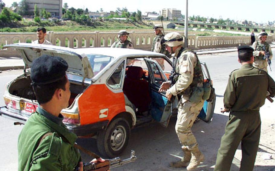 Troops from 2nd Battalion, 503rd Infantry Regiment, out of Vicenza, Italy, and local police officers conduct a spot-traffic stop in Kirkuk, looking for contraband such as weapons and ammunition.