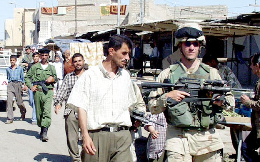 Capt. Arie Richards, commander of Company C, 2nd Battalion, 503rd Infantry Regiment, and a local police officer patrol the market at Kirkuk, Iraq. The Army started the joint patrols with local police last week.