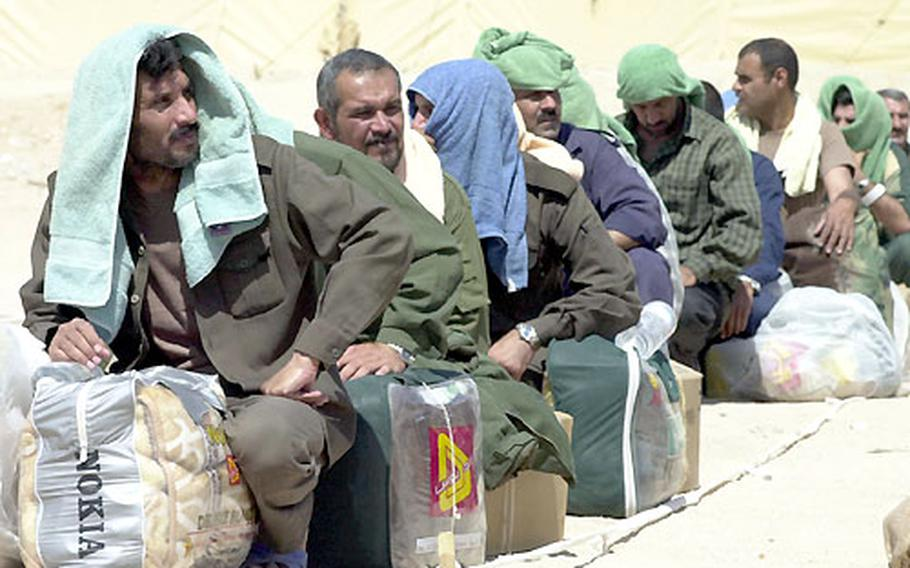 Former Iraqi prisoners wait for a ride home Tuesday at Camp Bucca