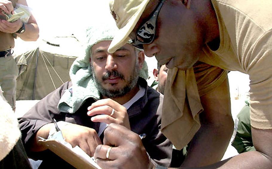 Maj. Marshall Bacote checks an Iraqi man off his list Tuesday during a release of prisoners at Camp Bucca.