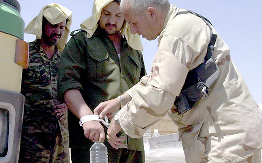 Cutting the identification bracelet from an Iraqi prisoner, 800th Military Police Brigade 1st Sgt. Mickey Michelino, of New York, N.Y., frees the former captive and directs him to a nearby bus. Each prisoner received food, water, cigarettes and $5 cash.