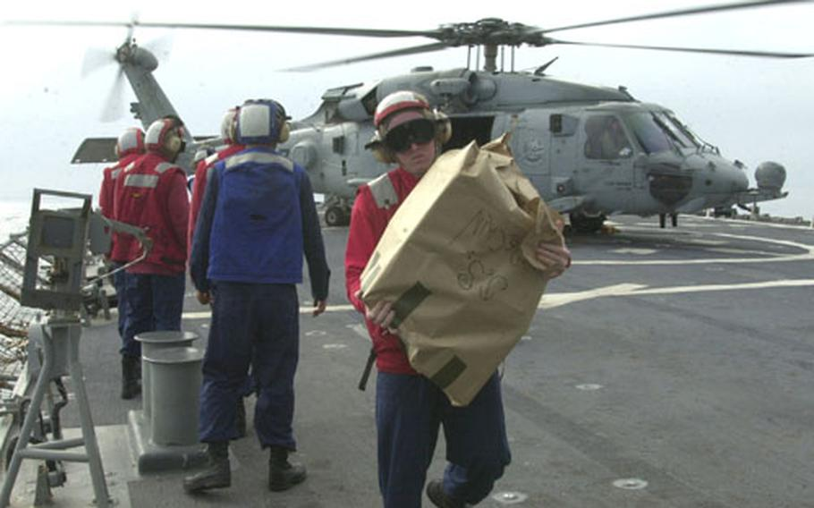 Sailors from the USS John S. McCain carry in spare parts brought on board by helicopter. The McCain returned to Yokosuka on May 6 after a long deployment to the Persian Gulf.