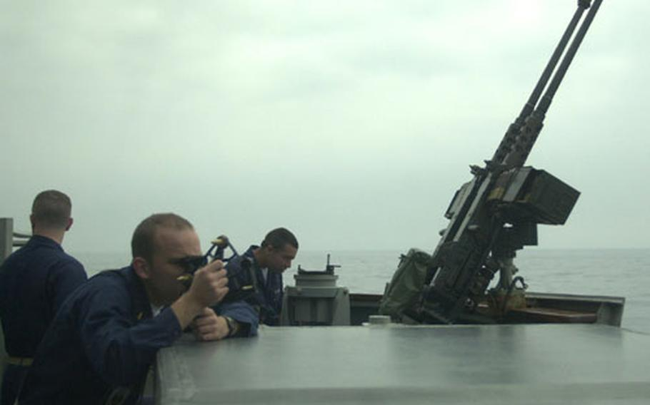 Ensign William Carr (foreground) takes a sextant reading as the USS John S. McCain approaches a Navy fueler off the coast of Japan. The McCain returned from the Persian Gulf on May 6.