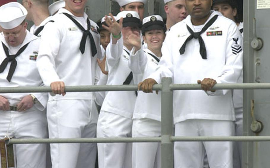 Sailors of the USS Cowpens wave as they return to Yokosuka Naval Base.
