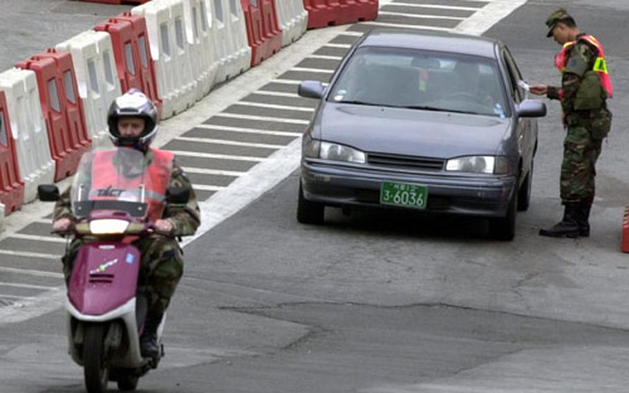 A soldier drives a scooter onto Yongsan Garrison, South Korea. Base officials have tightened rules on such vehicles in an effort to increase safety and curb underage driving.