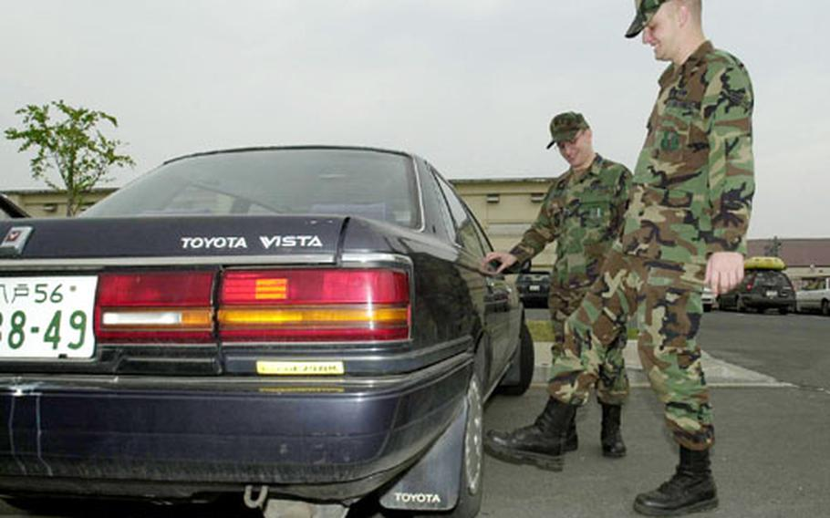 Like any prospective car owner, Airman 1st Class Aaron Bethard kicks the wheels of a Toyota Vista as owner, Senior Amn. William Miller, watches. Miller is donating his high-mileage car free of charge to Bethard under a new program sponsored by Misawa's First Term Airmen's Center.