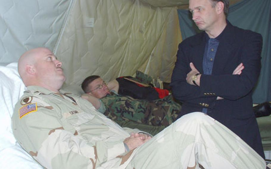 Army Sgt. Richard Crump, a patient at Fleet Hospital Eight in Rota, Spain, talks with Dr. William Winkenwerder, assistant secretary of Defense for Health Affairs on Thursday at Naval Station Rota, Spain. Winkenwerder visited the hospital staff and talked with some of the patients at the tent hospital on base. Crump is member of the North Carolina-based 1454th Trans Company, which is deployed in Iraq.