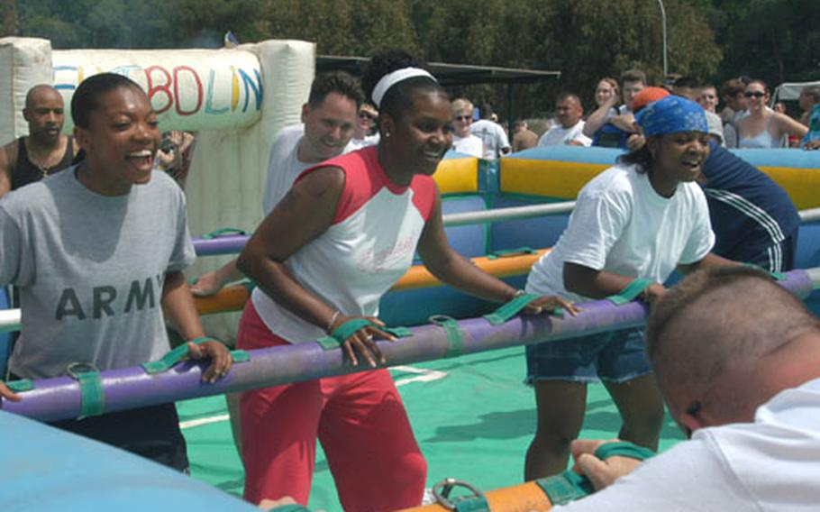 The human foosball competition drew lots of laughs Friday at the Armed Forces Olympics at Carney Park in Naples, Italy. Playing from left were Army Sgt. Shonda Haddock, 27, from Greeneville, N.C.; Air Force Staff Sgt. Sabrina Crawford, 28, from Charlotte, N.C.; and Navy Petty Officer 2nd Class Janina McQueen, 24, from Greensboro, N.C.