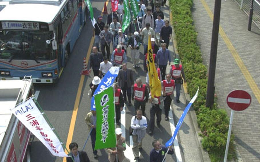 Japanese protesters march toward the front gate of Yokosuka Naval Base on Saturday.