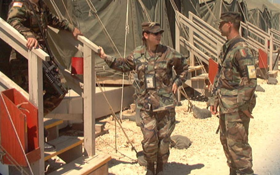 Sgt. Leandro Diaz, translator Eve Niceva and Pvt. Philip Robertin talk outside one of the living areas at Camp Bondsteel in Kosovo. Military commanders are using the utilitarian post as a model for new bases planned for Eastern Europe.