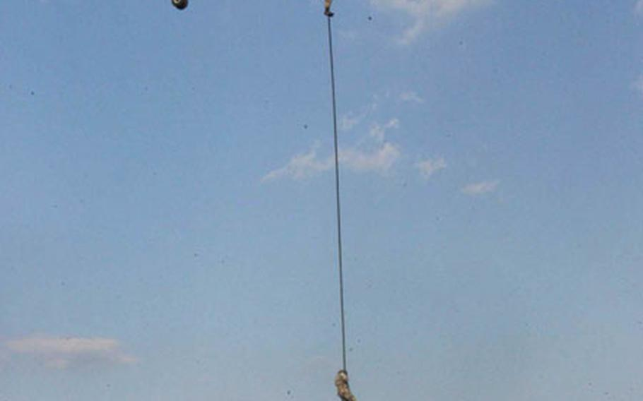 Philippine servicemembers rappel 70 feet from a U.S. Marine CH-46 as part of a fast rope jump during Balikatan 2003 at Clark Air Base, Philippines.
