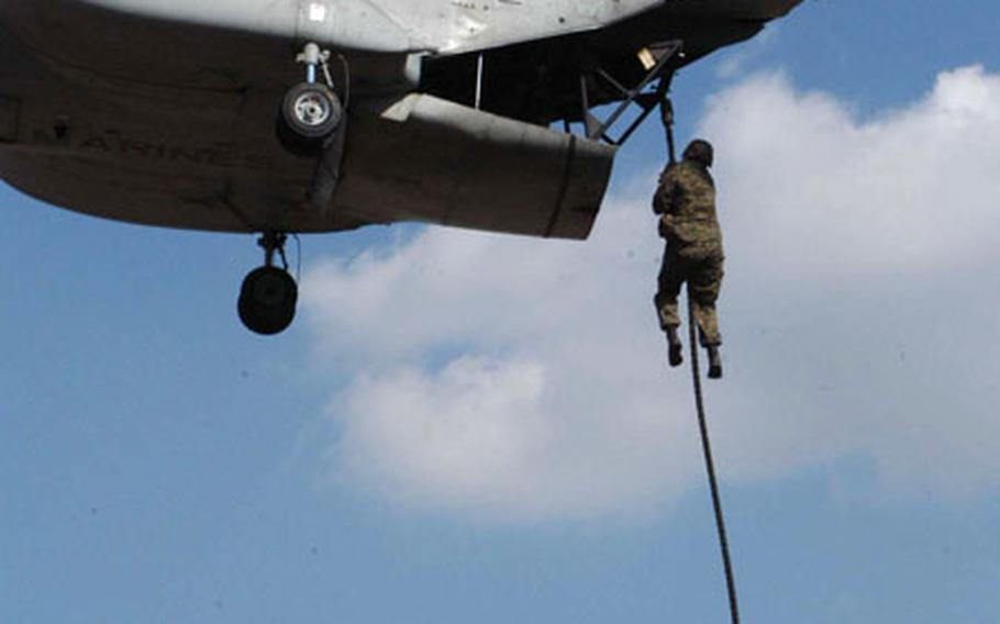 A U.S. Marine rappels 70 feet from a CH-46 as part of a fast rope jump during Balikatan 2003 at Clark Air Base, Philippines.