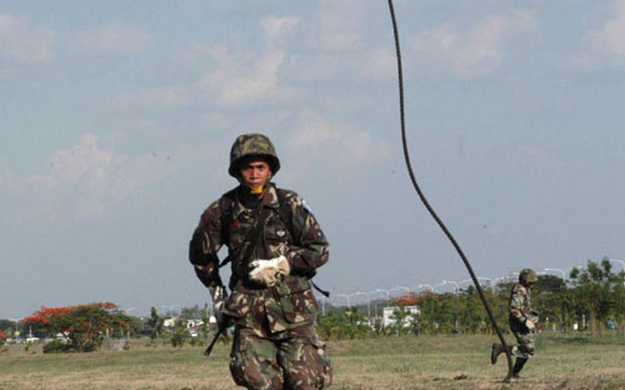 Philippine servicemembers hit the ground running after a 70-foot rappel from a U.S. Marine CH-46.