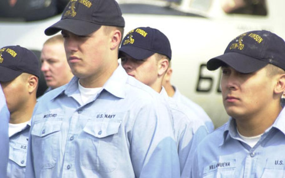 USS Carl Vinson sailors, such as Airman Matthew McCord (left) and Airman Anthony Villanueva, didn't appear very happy while going through the rigamarole of uniform inspection — the tradeoff for a few days of liberty.