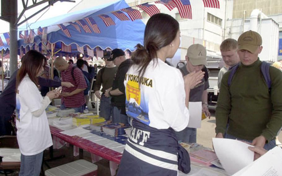 USS Carl Vinson sailors swarm the Morale, Welfare and Recreation tables minutes after disembarking from the liberty boat at Yokosuka Naval Base Saturday. They grabbed up train maps and directions to such tourists spots as Kamakura and Yokohama.