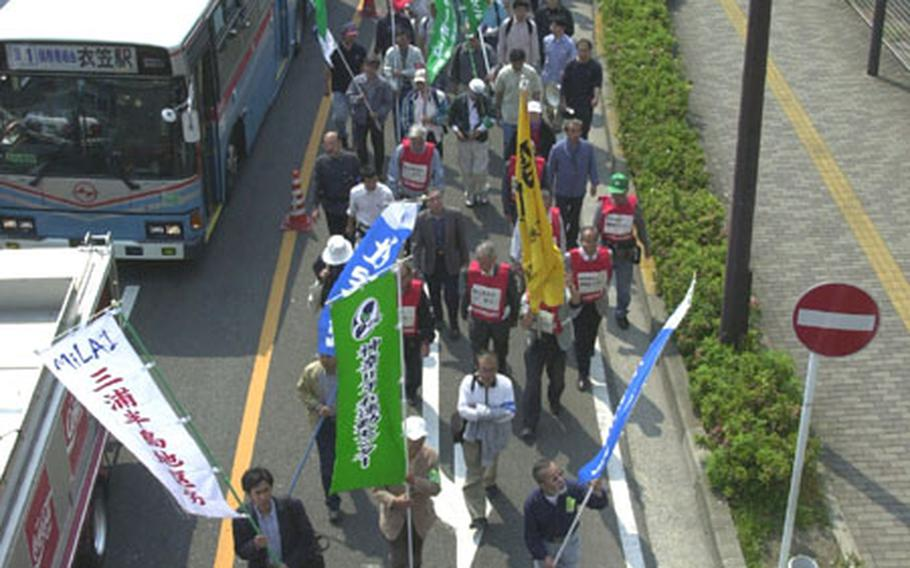 Protesters march toward the front gate of Yokosuka Naval Base on Saturday.