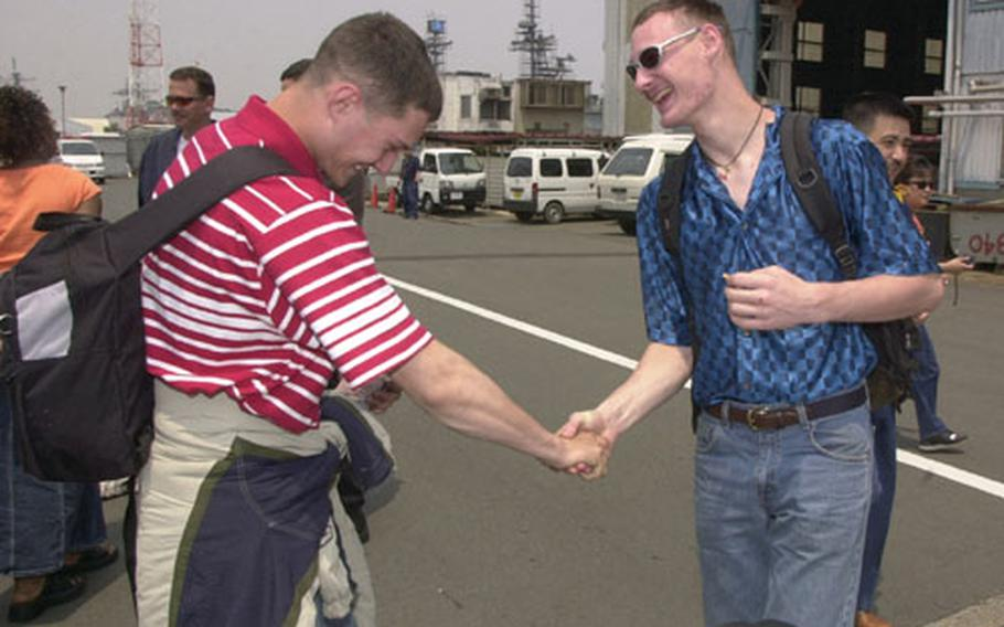 With a hearty and gregarious handshake after being apart for 1½ years, the USS Carl Vinson's Petty Officer 3rd Class Richard Shilling, left, greets his older brother, Petty Officer 3rd Class Matthew Shilling of the USS Kitty Hawk, on Saturday at Yokosuka Naval Base's Pier 3.