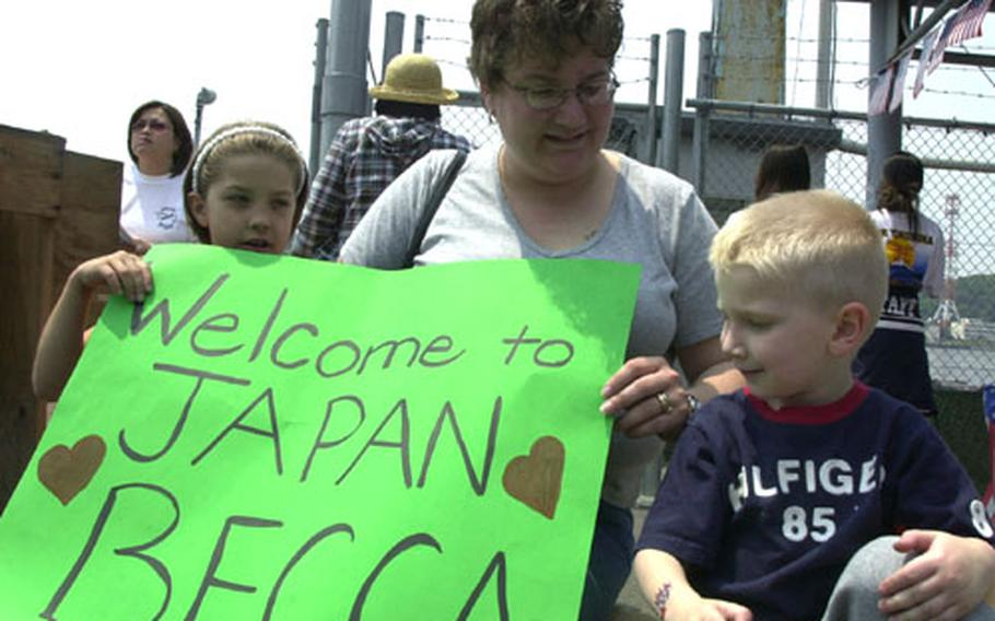 Niki Ruscitto reunited with her sister, Airman Rebecca Sullins from the USS Carl Vinson's air division, after the Vinson anchored in Yokosuka on Saturday. Before Sullins stepped ashore from a liberty boat, Ruscitto waited with her daughter, Jamie, and son, Clayton, proudly displaying their bright green poster welcoming Sullins to Japan.