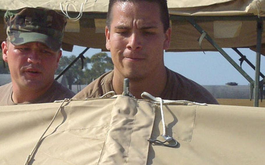 Petty Officer 3rd Class Gonzalo Chavez helps dismantle a tent Friday at Naval Station Rota, Spain.