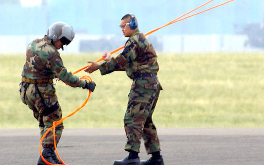 Staff Sgt Calvin Warner, right, a life support specialist, assists Staff Sgt. David Jewell during helicopter rappel training.