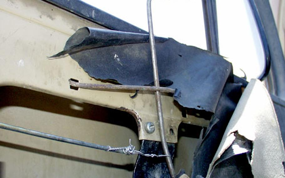 Air Force mechanics used wire and steel cables to rig a door handle on this old Iraqi truck.