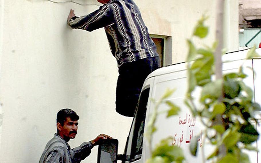 When it comes to health care needs in Iraq, shortages come in all shapes and sizes. For these two maintenance workers at Kirkuk General Hospital in northern Iraq, they're short a ladder, so they improvise by using the hood of an ambulance to fix an outdoor light.