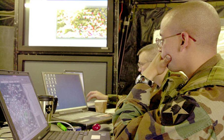 Sgt. Robert Gray (front) and 1st Lt. Stephen Sams work in the effects cell of the division headquarters Sunday during the Warfighter exercise, which tests the command and control of the division during a computer simulated war game.