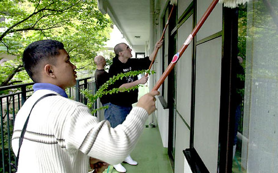 Sailors from the USS Carl Vinson clean the windows of a Yokosuka, Japan, nursing home as part of a community relations project Tuesday. Some sailors have been spending their port-call time helping others.