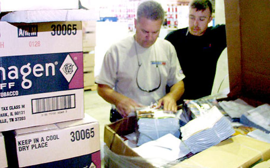 Dennis Hatcher, manager for the Army and Air Force Exchange in Iraq, and worker Fritz Eischenhauer check out a shipment of magazines headed for tactical field exchanges in Iraq.