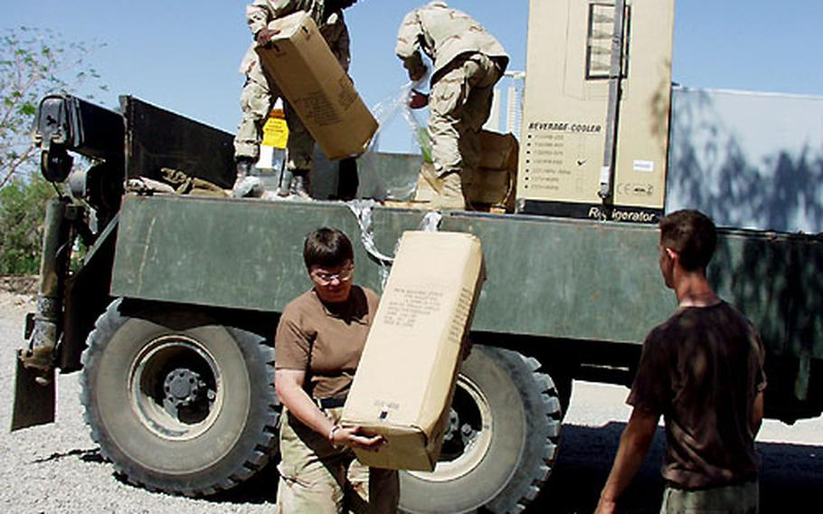 Cynthia Grzybowski, manager of the new AAFES store at Victory Camp in Baghdad, Iraq, helps unload merchandise.