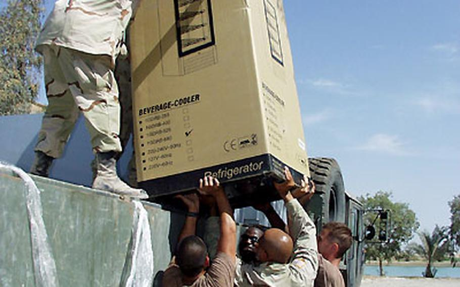 Army and Air Force troops unload a new refrigerator at the Army and Air Force Exchange Service store, set to open Friday at Victory Camp in Baghdad.