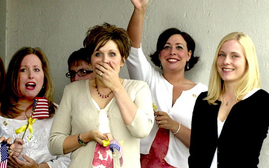 Wives of members of the 159th Medical Company, out of Wiesbaden, Germany, react as their husbands get off the bus that brought them from Ramstein Air Base upon their return from Operation Iraqi Freedom.