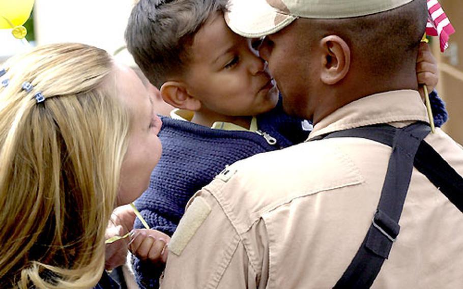 Domenic Espinoza, 2½, gives his dad, Chief Warrant Officer 2 Michael Espinoza, a kiss as mom Anja watches.