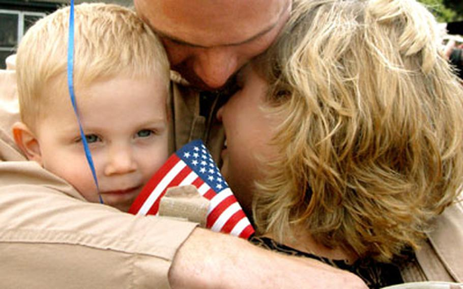 Sgt. Kerry Boese and wife Sheila share a tender moment as son Samuel, 22 months, just seems happy to have dad home. Boese and other members of the 159th Medical Company, 421st Medical Evacuation Battalion, returned to Wiesbaden, Germany, from Operation Iraqi Freedom on Wednesday.