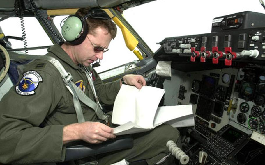 Capt. Rusty Evers checks over paperwork while his KC-135R tanker flies on autopilot 21,000 feet over the Sea of Japan Tuesday. He was flying an air refueling mission for American and Japanese fighter aircraft flying in the Cope North exercise.