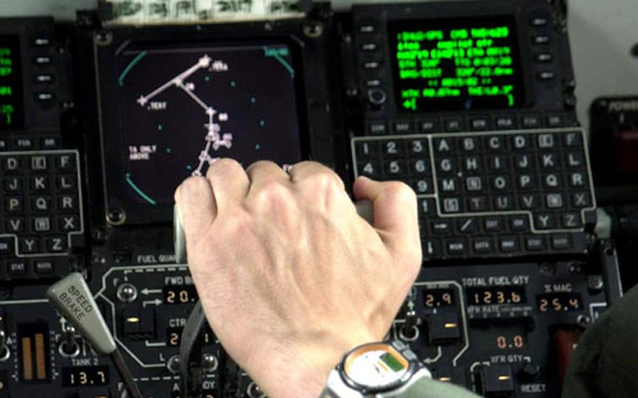 The hand of 1st Lt. Jeff Guttman adjusts engine throttles in the cockpit of a KC-135R tanker flying over the Sea of Japan during Cope North exercises Tuesday.