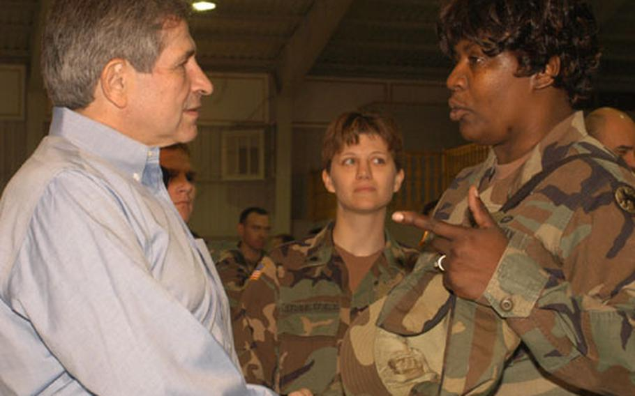 The U.S. Deputy Secretary of Defense, Paul Wolfowitz, left, shakes hands with Staff Sgt. JoAnn Brown of Task Force Medical Eagle, right, during his visit to Bosnia on Armed Forces Day. He signed the arm cast of Spc. Jennifer Stubblefield of 35th Military Police Company, center.