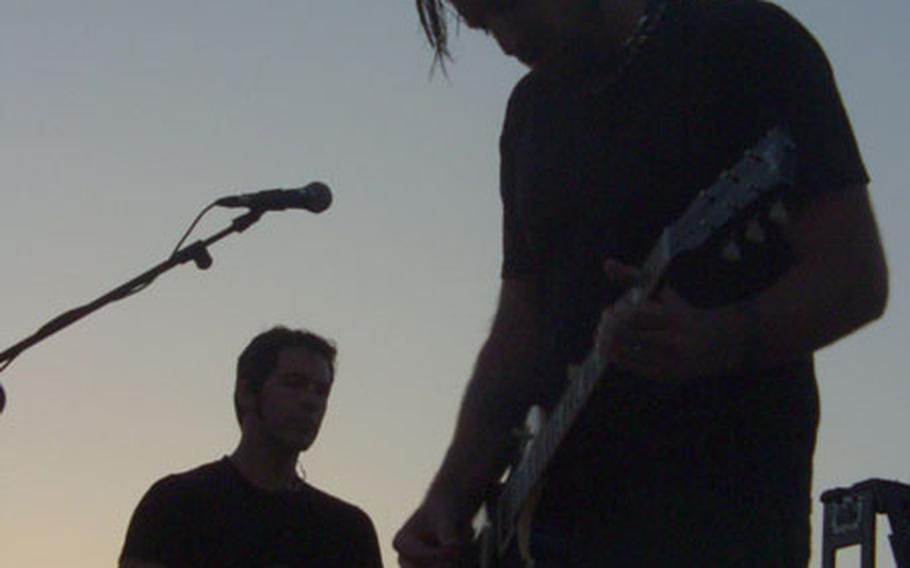 As the sun sets, Dishwalla guitarist Rodney Browning Cravens, right, performs with singer J.R. Richards, in the background.