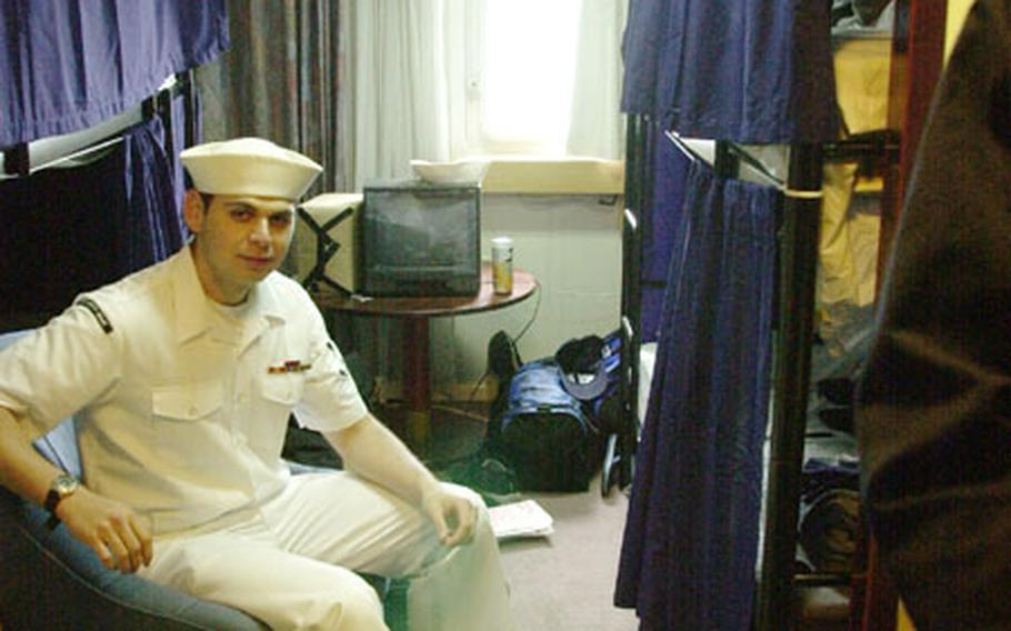 Petty Officer 3rd Class Israel Lopez takes a break in his new room on board the berthing barge Olympia.