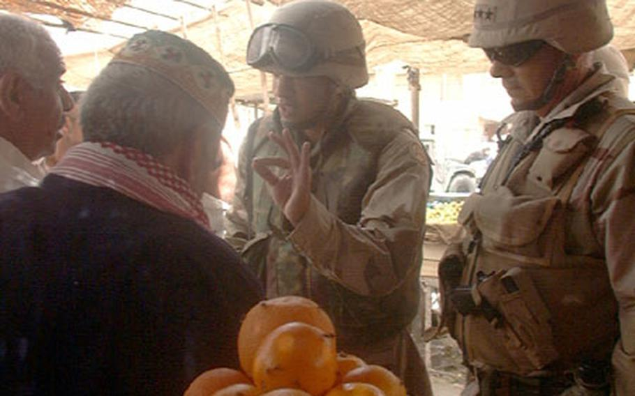 V Corps Commander Lt. Gen. William S. Wallace, with the help of interpreter Sgt. Daeman Harris, talks with a leader at a market in the Hi-Salam area of northwest Baghdad.