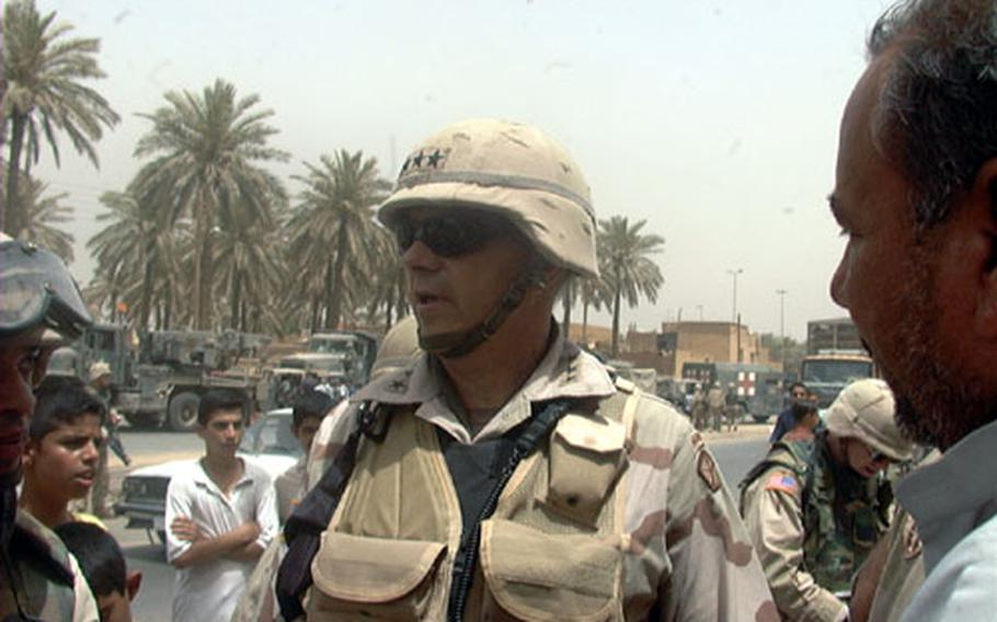 V Corps Commander Lt. Gen. William S. Wallace talks with an Iraqi merchant in Hi-Salam, a Shiite neighborhood in northwest Baghdad. Wallace sent Army medics, seen in background, and engineers to the neighborhood to treat people and clean up the area.