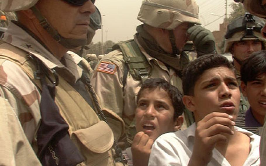 V Corps Commander Lt. Gen. William S. Wallace listens to a boy talking about shortages of school supplies in his northwest Baghdad school.