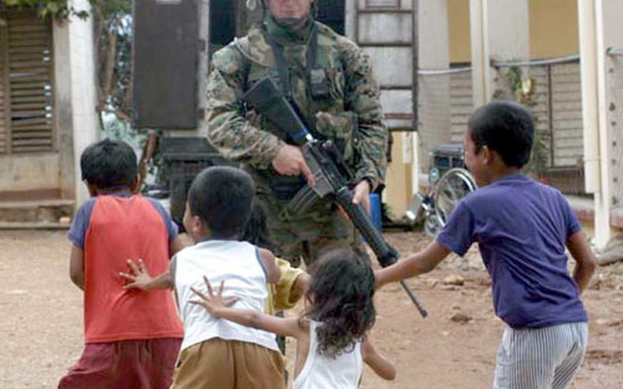 Armed Marines watch children play during a Medical Civil Action Project, or MEDCAP, held by U.S. and Philippine forces near Zamboanga City in the Southern Philippines. Military and civilian medical personnel treat villagers while a contingent of Marines patrols the surrounding village and guards the grounds of the MEDCAP. Travel to the location requires a multi-vehicle convoy including armored humvees. Occupants wear Kevlar body armor and each vehicle must have several weapons inside.