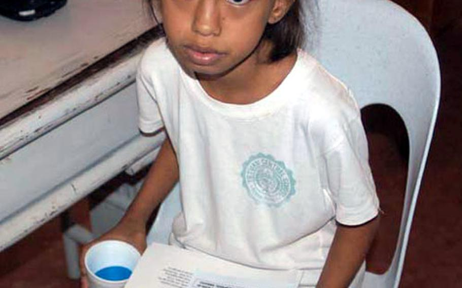 A young girl, waiting for a checkup, carries tips for preventing SARS during a Medical Civil Action Project, or MEDCAP, held by U.S. and Philippine forces near Zamboanga City in the Southern Philippines.