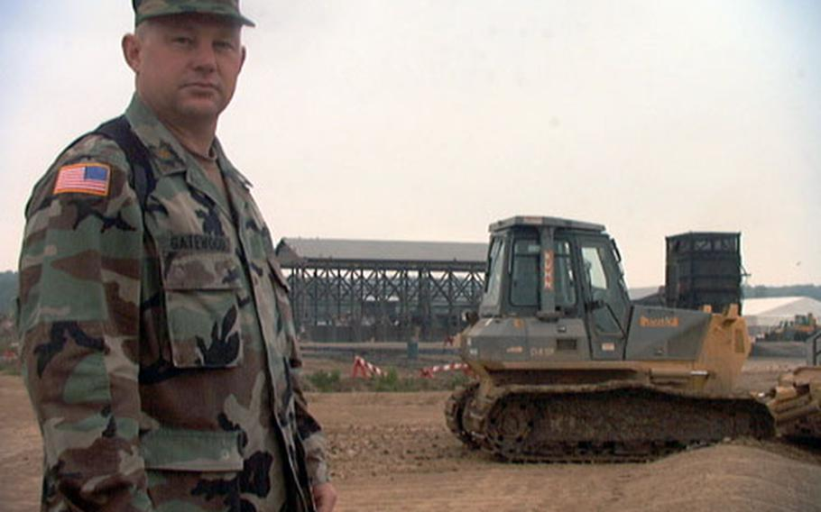 Maj. Bill Gatewood watches as a bulldozer smooths out a field that will soon be covered in mountains of sewage sludge. Gatewood, a reservist who is a farmer in civilian life, is using composting techniques to rid Camp Bondsteel of waste that would otherwise have to be incinerated at a much higher cost.