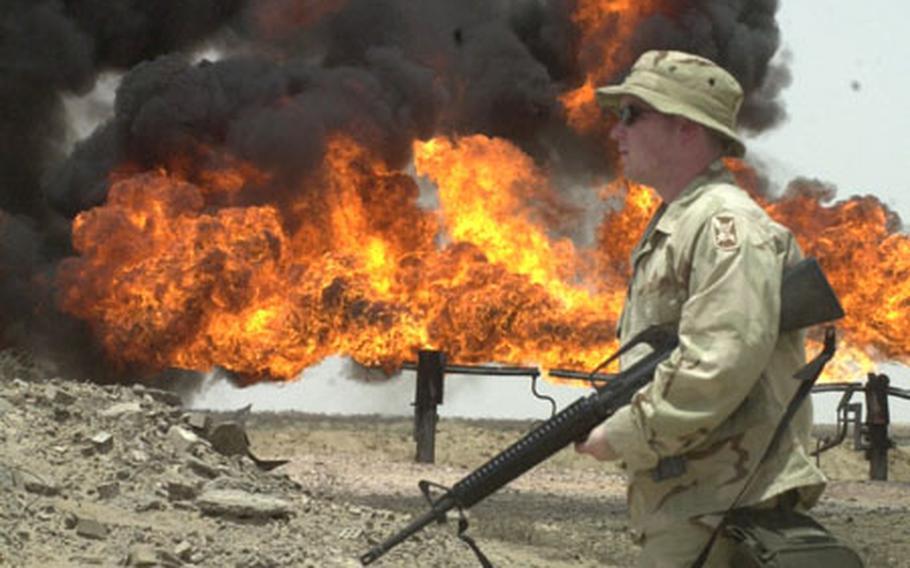 Spc. Joseph Feagin, 25, of Charleston, S.C., strolls past burning gas fires at an oil processing plant near Rumallah, Iraq.