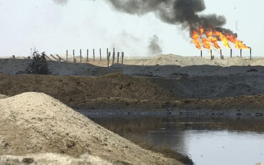 Lakes of bubbling crude surround an oil processing plant near Rumallah, Iraq, as necessary gas fires burn in the distance. The U.S. Army Corps of Engineers is overseeing a vast project to restore Iraqi oil and fuel production to help the local people.