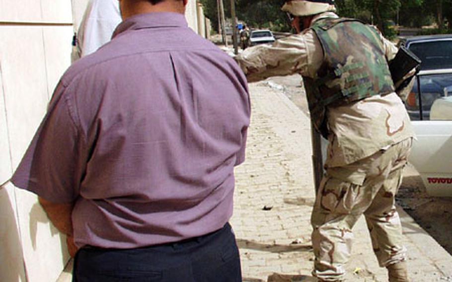 Staff Sgt. Michael Lugo pats down Iraqi men after a traffic stop Saturday.